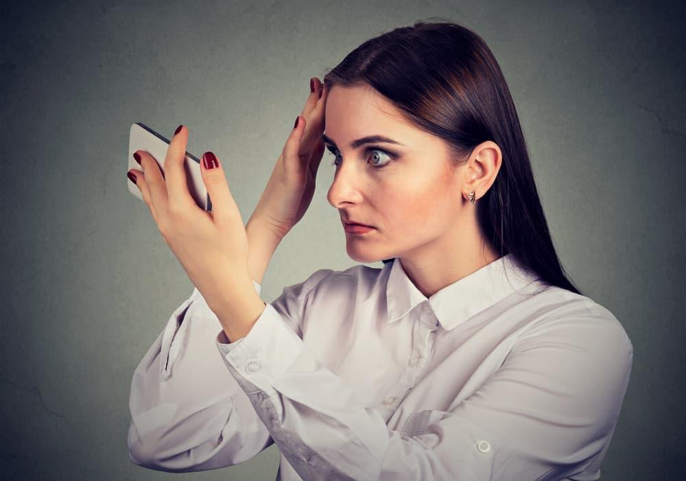 kobieta sprawdza włosy