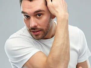 mężczyzna przeczesuje ręką włosy