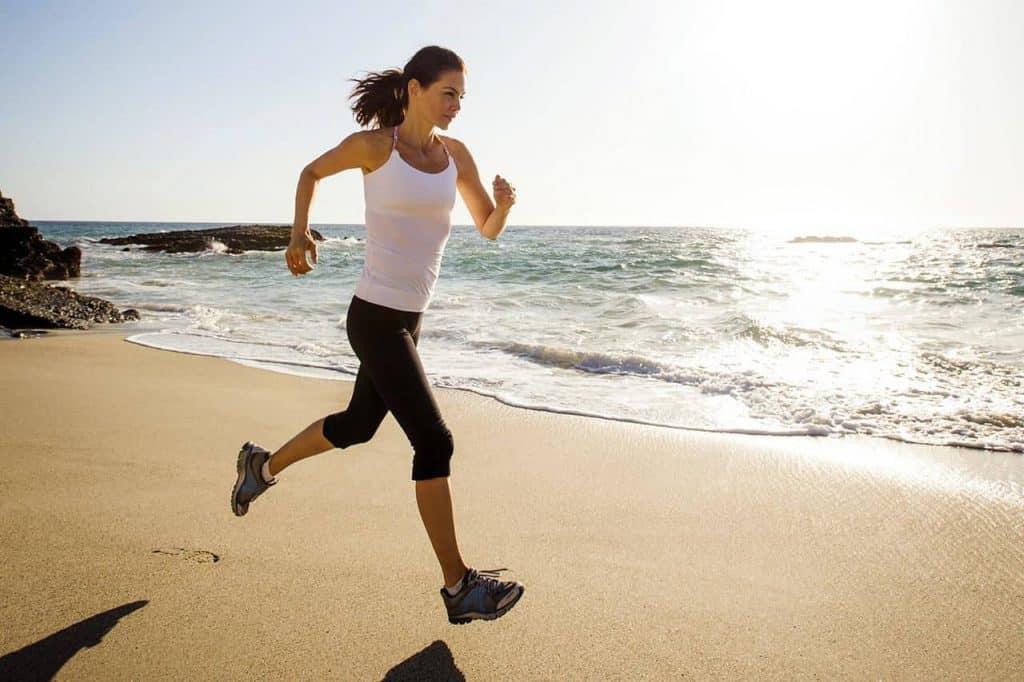 kobieta biegnie po plaży