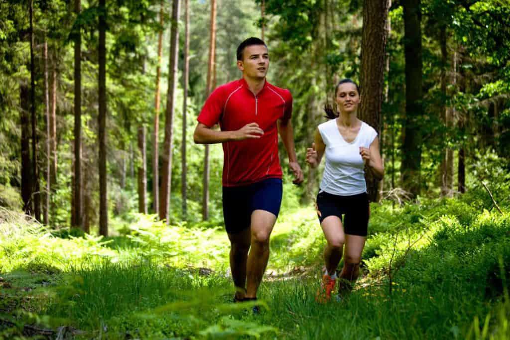 meżczyzna i kobieta biegają po lesie