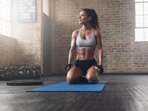 kobieta klęczy na macie do ćwiczeń