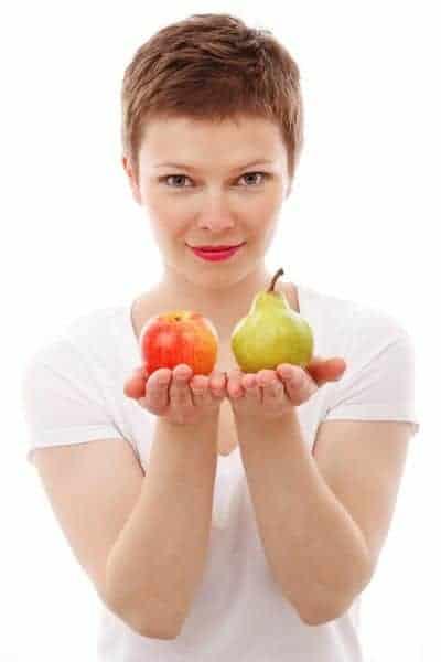 kobieta trzyma jabłko i gruszkę