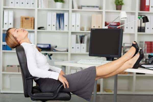 kobieta trzyma nogi na biurku