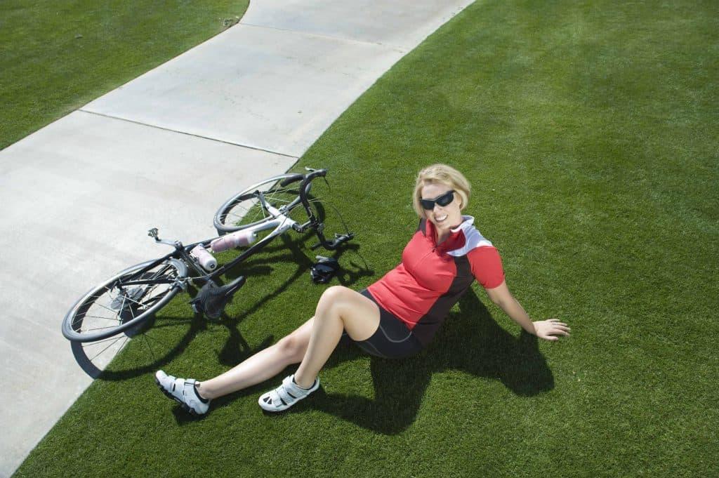 kobieta siedzi obok roweru