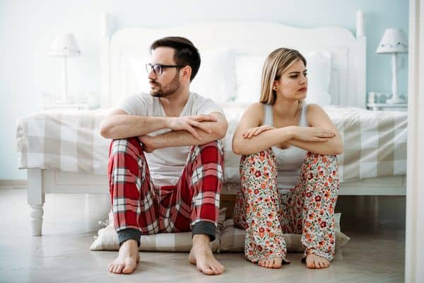 kobieta i mężczyzna siedzą przy łóżku