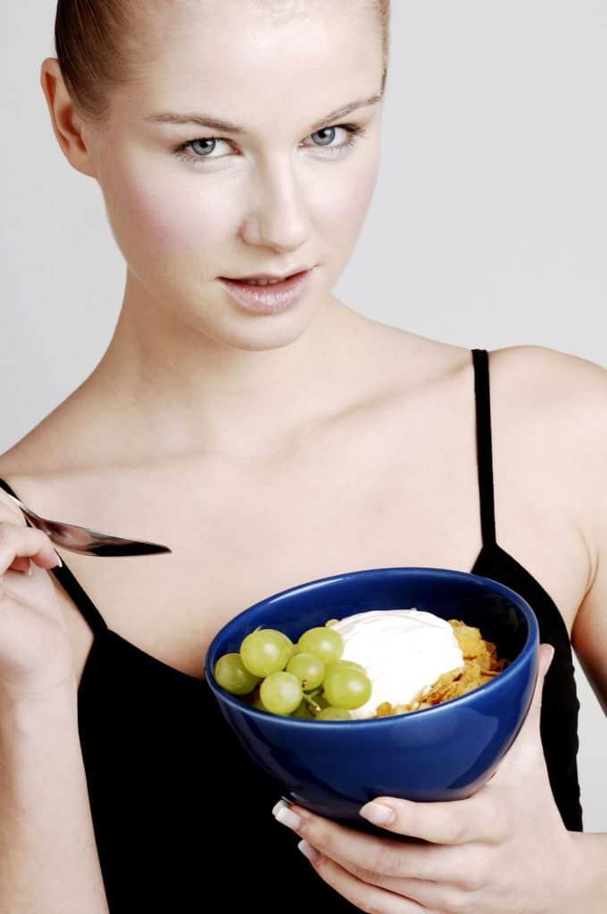 kobieta je płatki z owocami