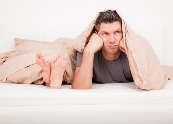 sfrustrowany mężczyzna w łóżku