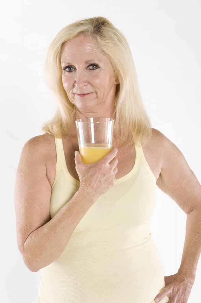 kobieta ze szklanką soku z cytryny