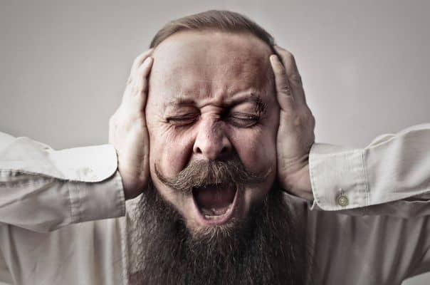 mężczyzna zasłania uszy