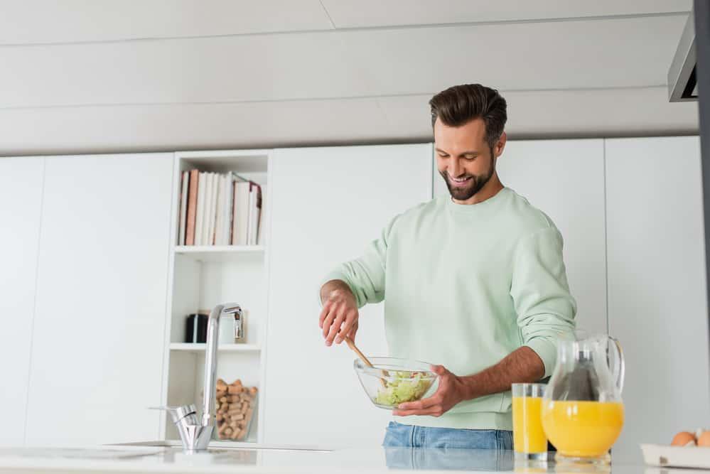mężczyzna robi zdrową sałatkę